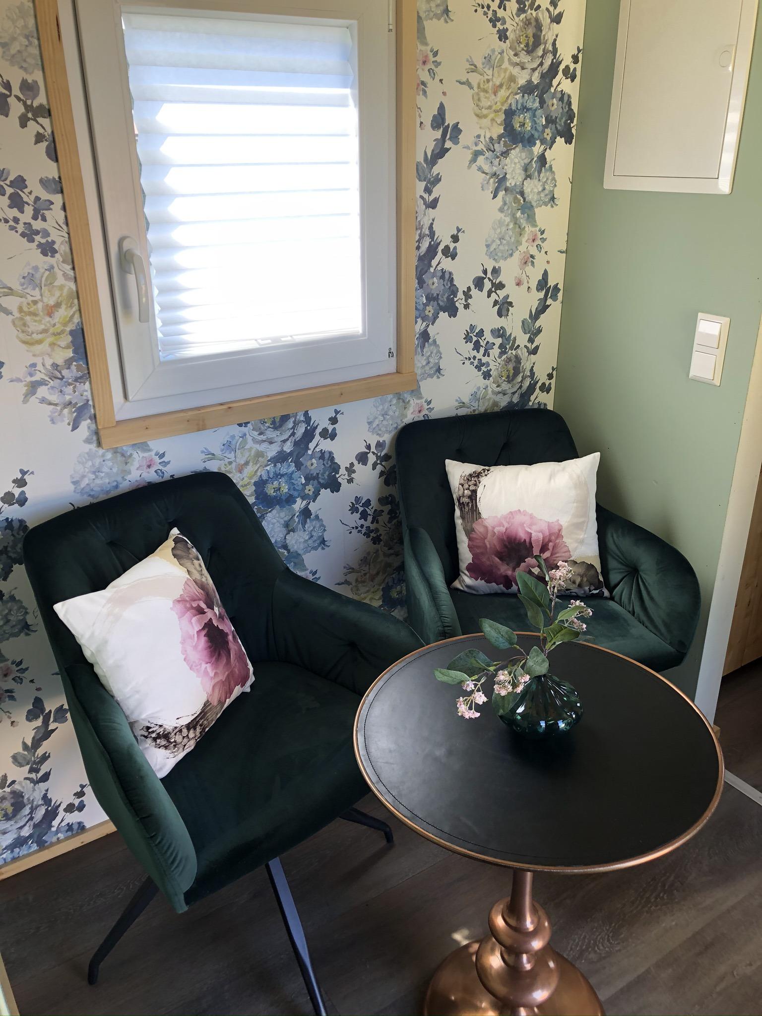 Die Sitzecke mit Sesseln und Tisch vor bunter Blumentapete