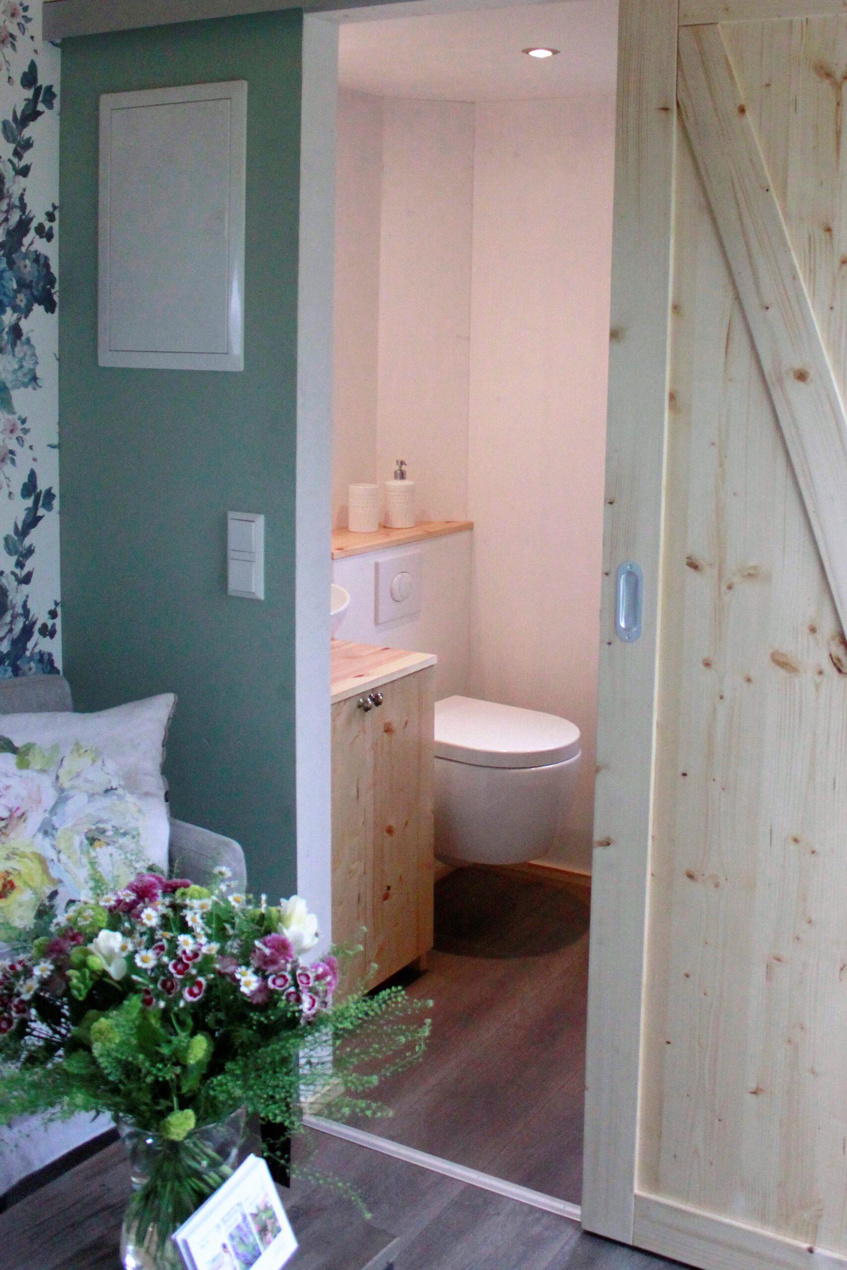 Die rustikale Holzschiebetür zum Bad des Tiny Houses Rhein