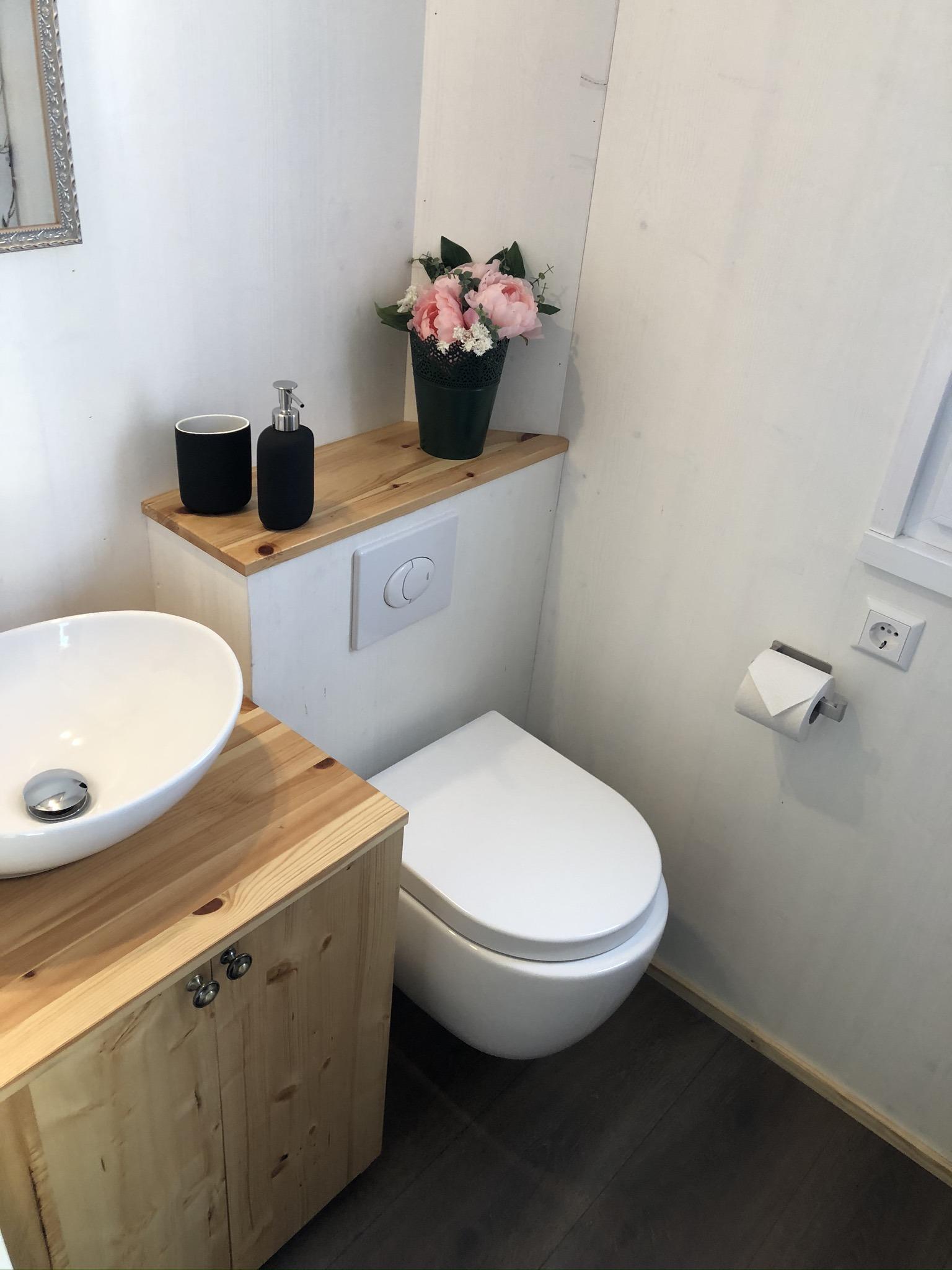 Blick ins Bad mit WC, Waschbecken und Unterschrank